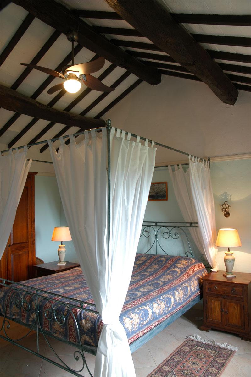 Gemütliches Schlafzimmer mit Himmelbett und Deckenventilator